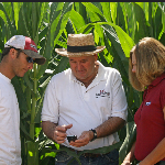 Agent keith perkins consults his GPS while talking to clients in a corn field