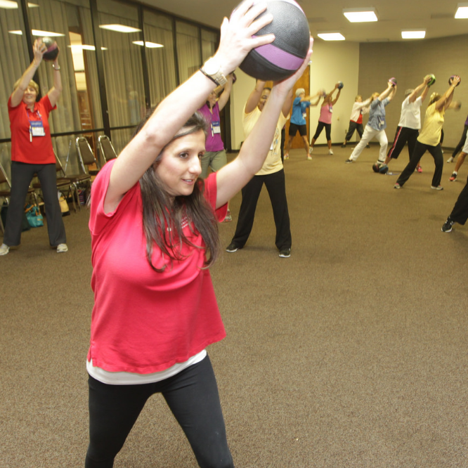 Wellness ambassadors use medicien balls to exercise in a group session