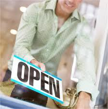 "Photo of a person holding a ""Now Open"" sign"