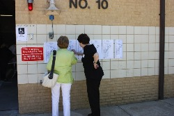 Two women review a sample ballot before voting.