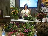 One white female standing behind a table filled with beautiful blooming plants