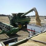 John Deere machine at side of field unloading harvested crop into large square containers