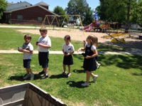 Kindergarten class looking for birds outside on the playground with binoculars.