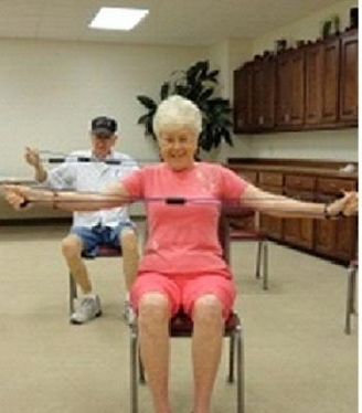 Older man and woman sitting in chairs while exercising their arms with stretch bands; woman in front wearing a peach colored short set with arms outstretched and a smile on her face; man is wearing a white shirt, blue jean shorts and a dark colored baseball cap; his arms are outstretched