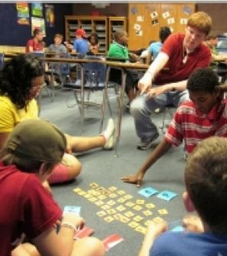 Teenage boys & girls sitting in the classroom floor playing a game; other students sitting in chairs in the background