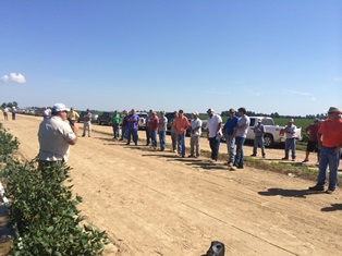 Group of farmers listening to specialist about field demonstration