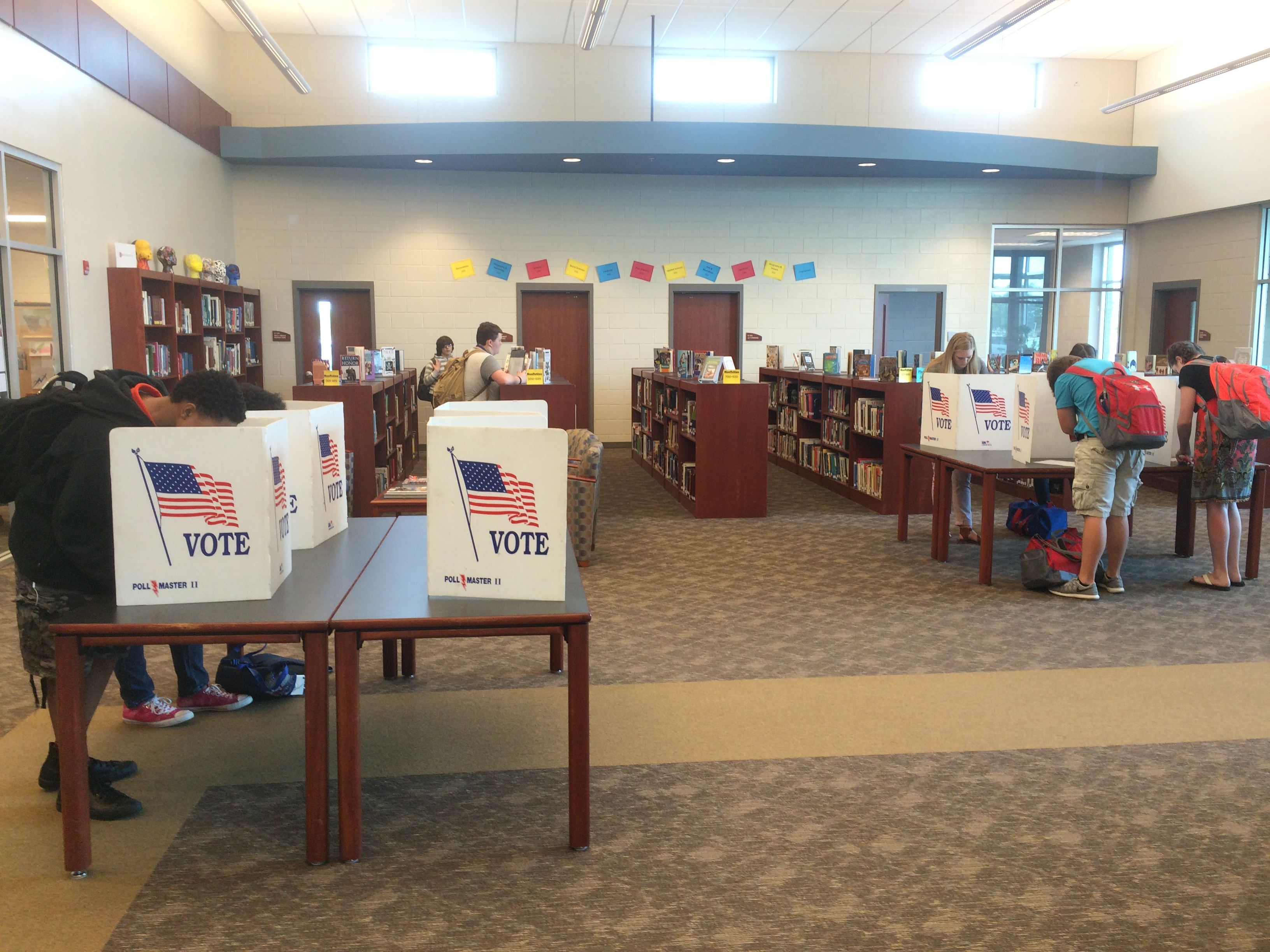 Library set up with voting ballot boxes and people voting