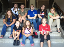 Image of several kids sitting on steps smiling at the camera