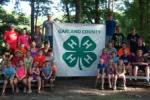 4-H youth sitting on bleachers with 4H banner at camp