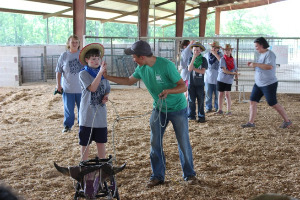 Adult instructing a child in Learning Roping