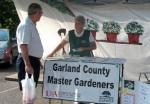 Garland County Master Gardener talking with man at exhibit tent in parking lot plants and sign