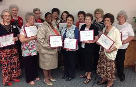 Thirteen ladies standing and holding award certificates.