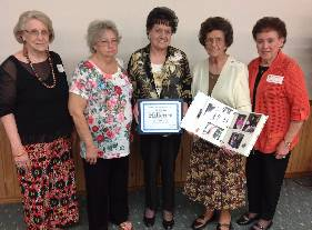 Five ladies standing in a row. One lady is holding an award certificate and one is holding an open scrapbook.
