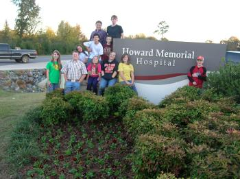 Group of eleven 4-Hers standing beside Howard Memorial Hospital sign