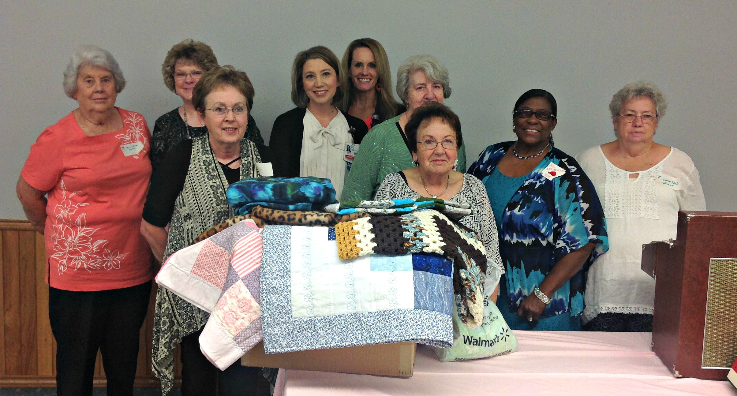 Nine ladies standing behind a table with a box filled with quilts.