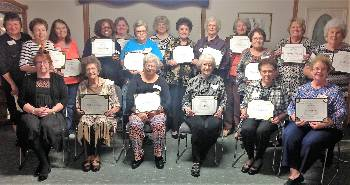 Six ladies sitting in chairs and 13 ladies standing behind them each holding award certificates.