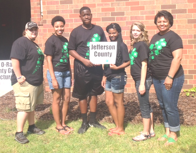 4 female 4-H'ers and one male 4-H'er standing with county agent Pia Woods holding Jefferson County sign