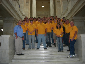 4-H Citizenship group standing on the steps at the Arkansas State Capitol building wearing yellow t-shirts.