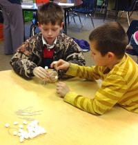 2 boys sitting at a table in a classroom making an animal figure using toothpicks and marshmallows