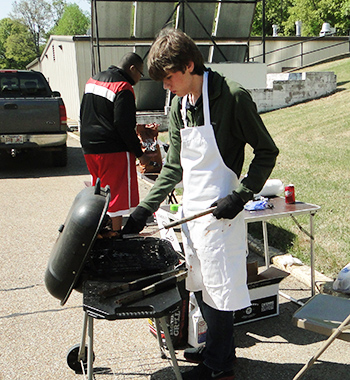 Teen boy wearing a chef apron while grilling on a charcoal grill & another teen boy in the background