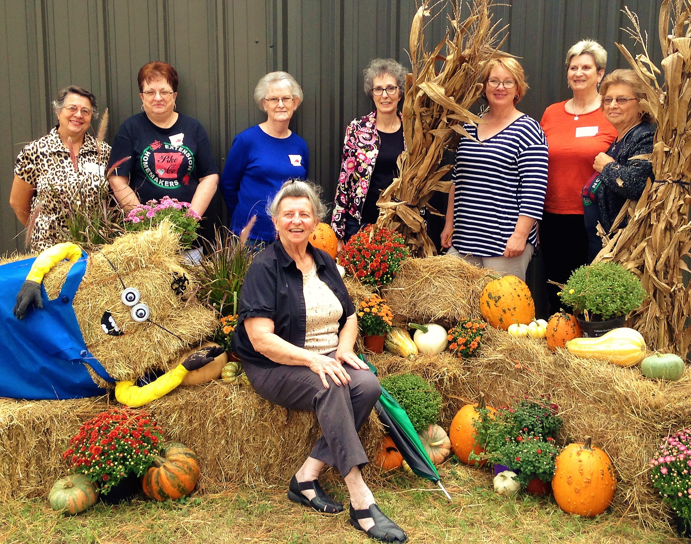 Pike County Members at District Fair posing for photo on decorative bales of hay