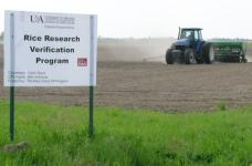 tractor plowing field participating in rice research verification program