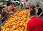 People standing all around trailer load of pumpkins at market
