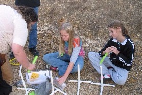 4-H youth sitting on the ground at a Rockets to the Rescue activity