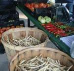 Vegetables displayed on shelves and in baskets at the Sevier County Farmer's Market