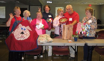 Group of Sevier County E H C members standing behind a table displaying their crafts