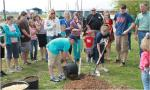 4H Youth and Leaders watching as two youth plant a tree for Arbor Day