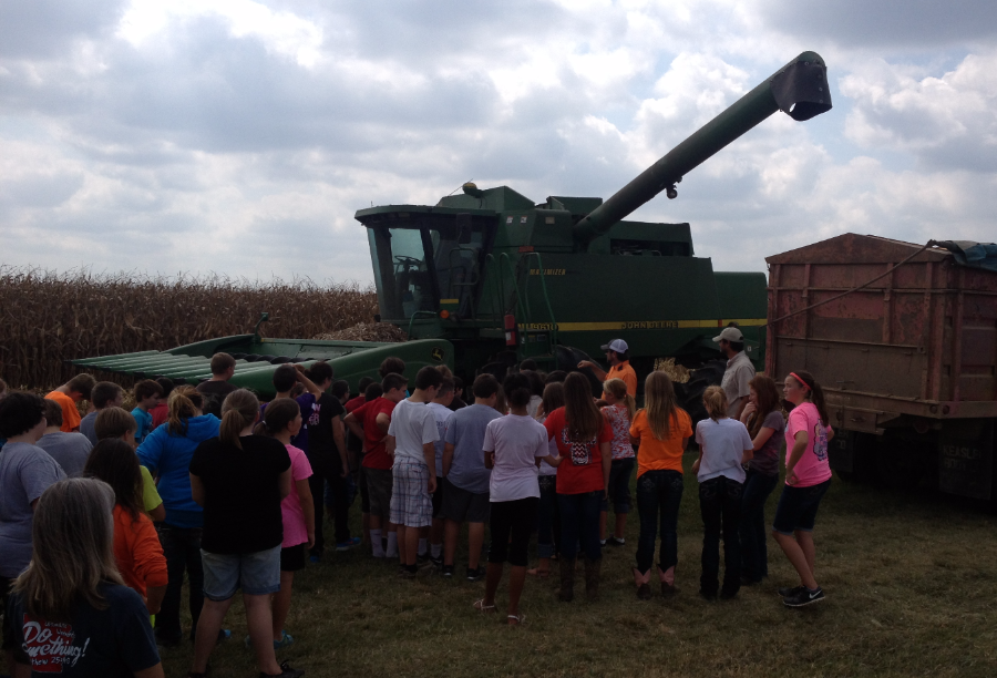 Agriculture Agent Brett Gordon with elementary school children watching a harvester fill a bin.