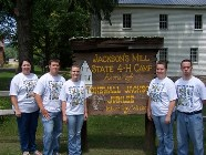 Image of 4-H Forestry at the National Contest standing in front of the Camp sign