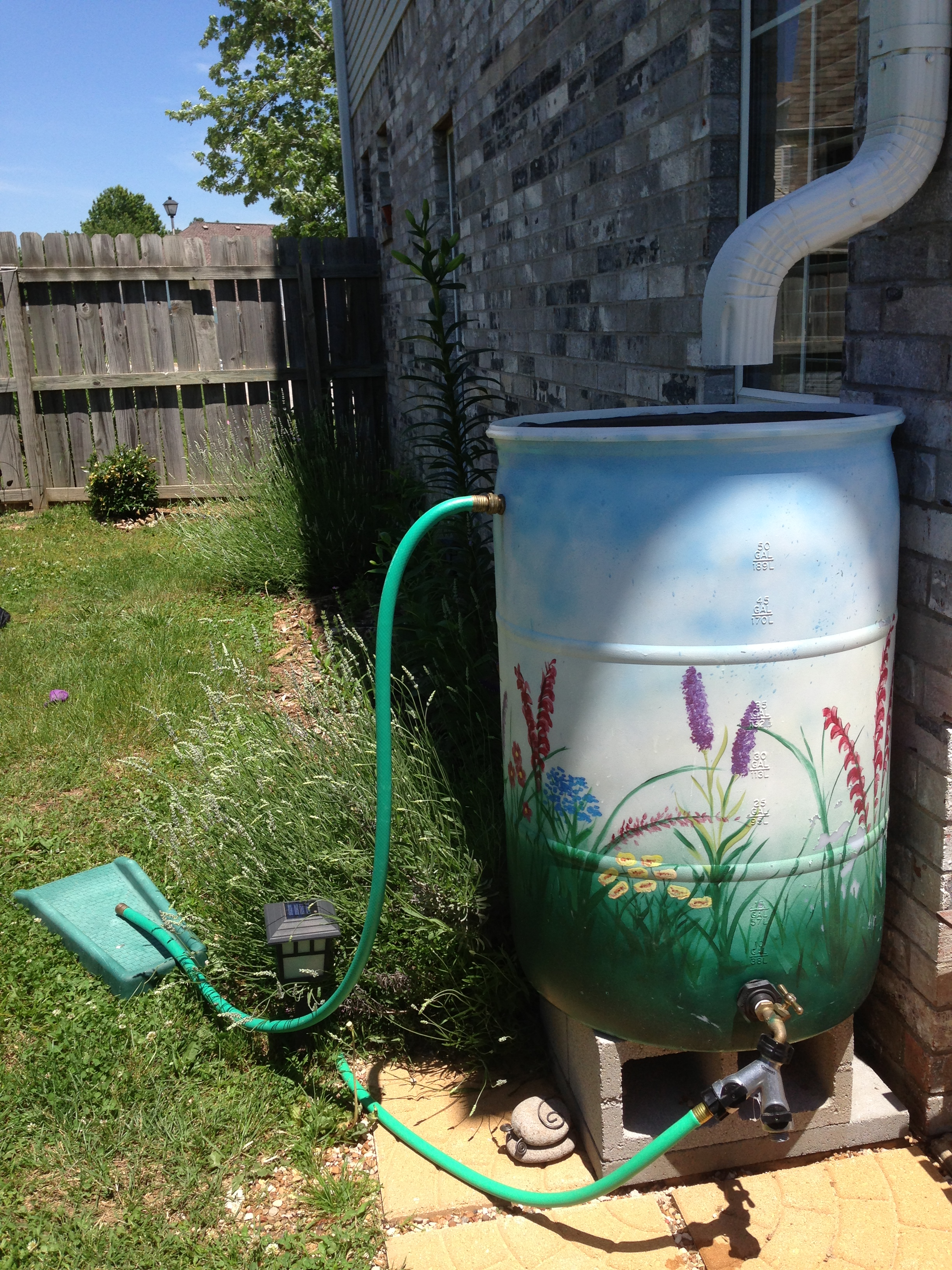 Painted rain barrel installed at home