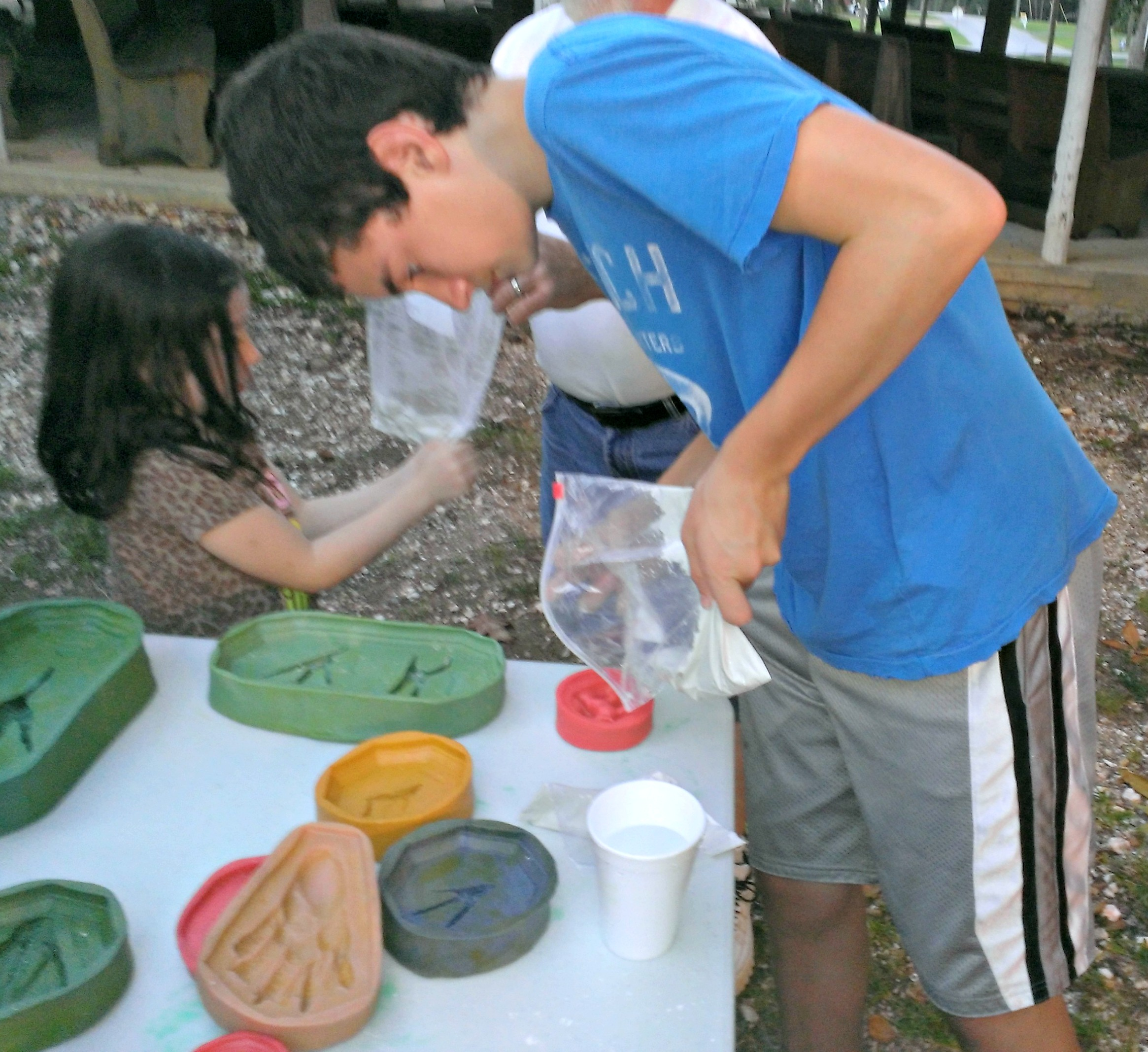 4-H male youth pouring plaster into wildlife track mold