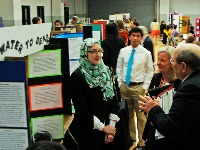 Central Arkansas science fair exhibit with student speaking with Extension employees