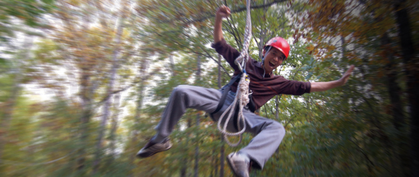 Young man riding a zip line.