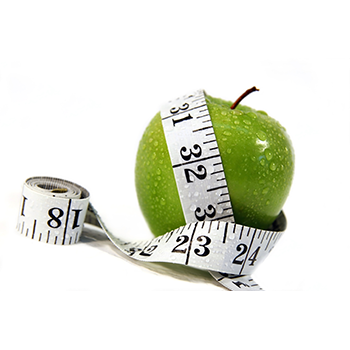 Freshly rinsed green apple with tape measure draped around
