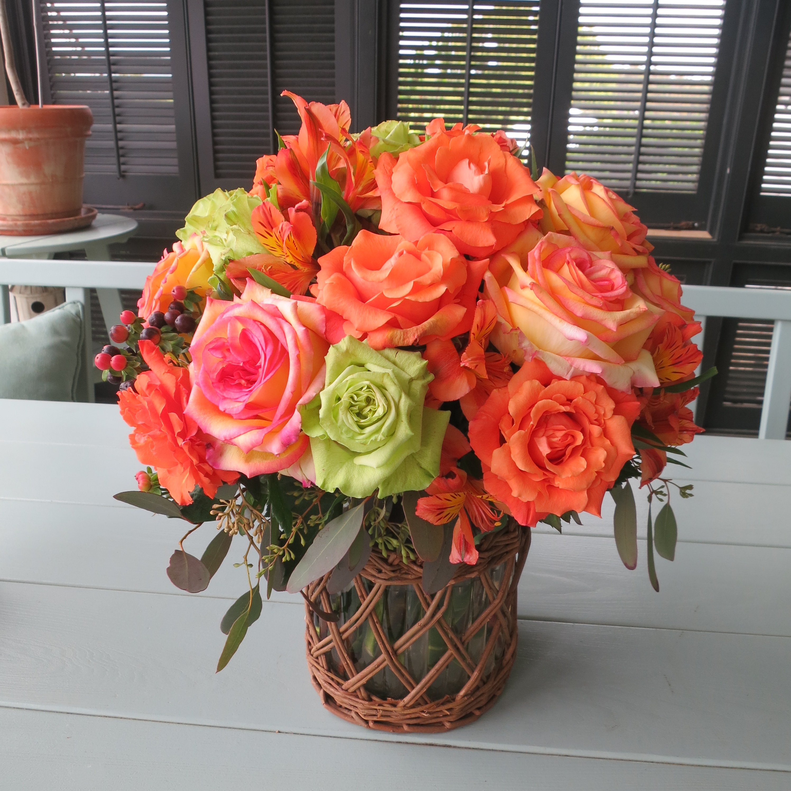 Photo of a bouquet of coral roses in a round vase