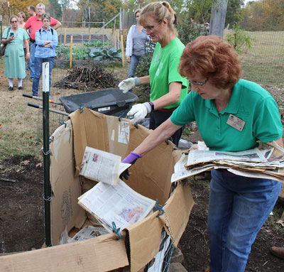 "Master Gardeners toss old newspaper into the bottom of their ""keyhole garden"" demonstration at the St. Joseph Community Garden"