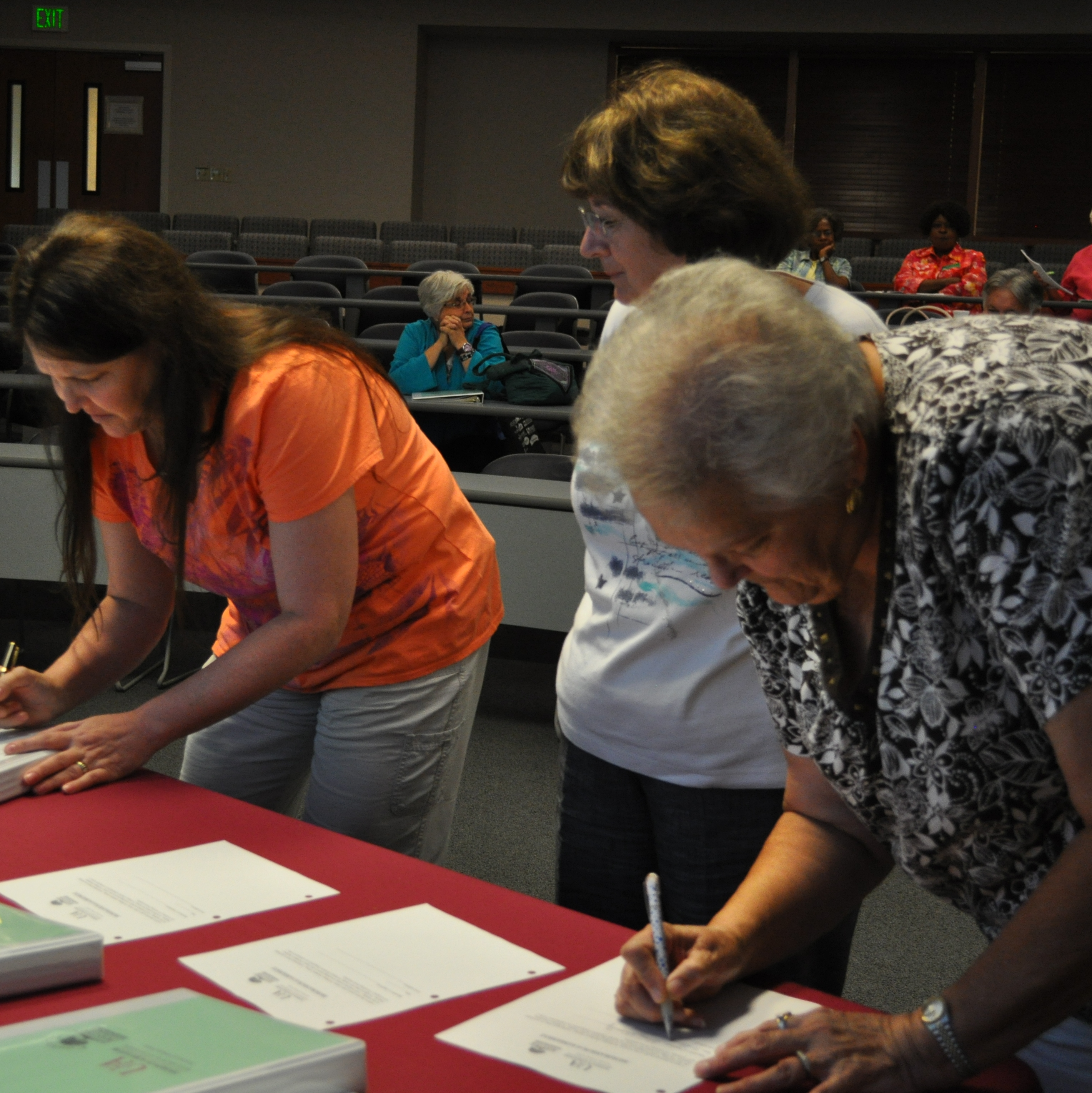 Photo of three Master Gardeners signing a list at a table